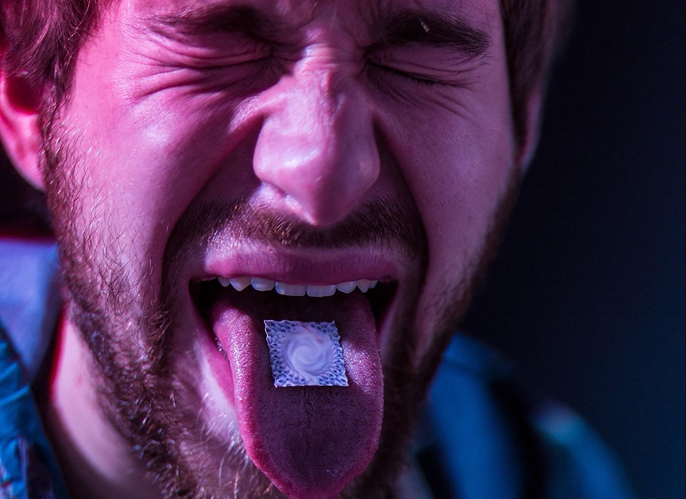 Close-up on junkie man taking LSD