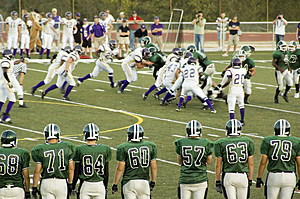 Players stand on the sidelines at a varsity high school football game.